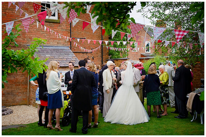 all the guests in the garden under the bunting at a multicultrual wedding in an English Garden