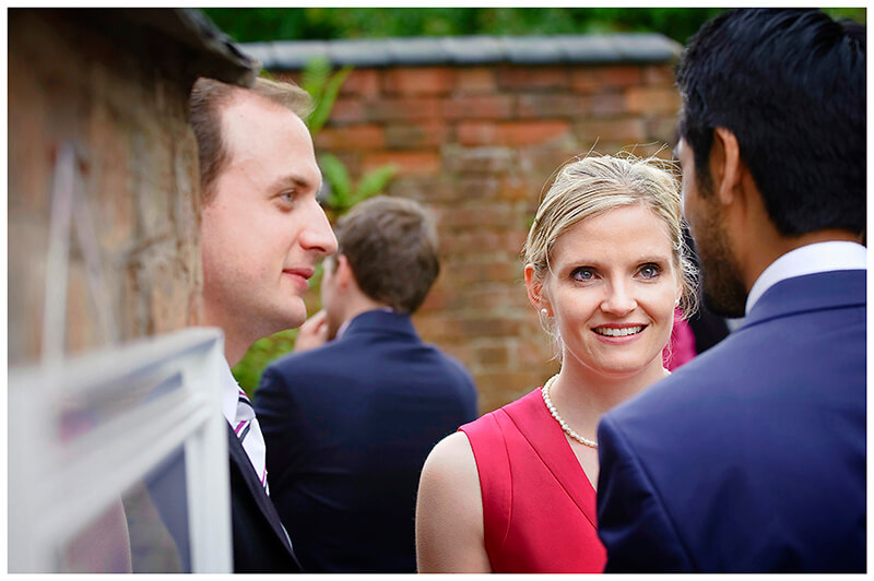 bridesmaid talking to male guests  during a Garden Wedding reception