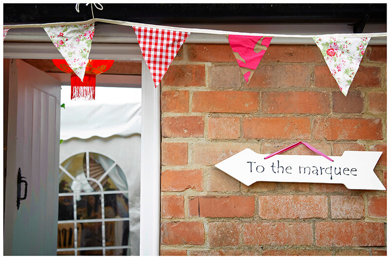 to marquee sign in garden under bunting