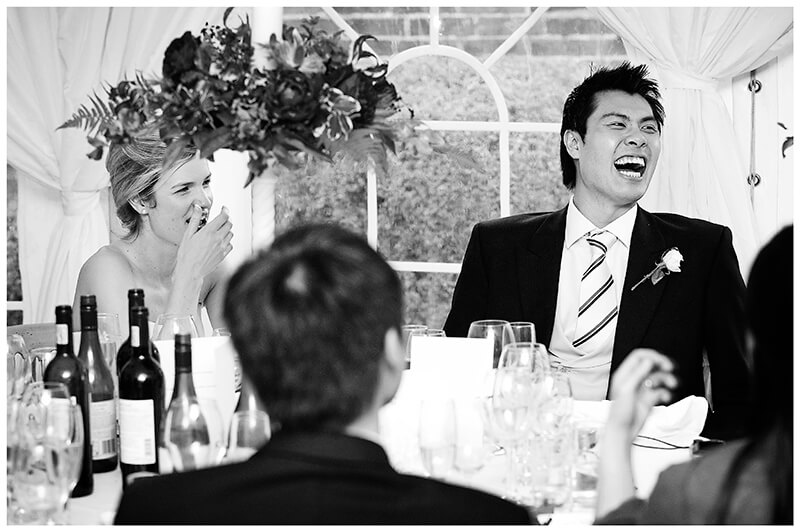 groom and bride laughing during speech