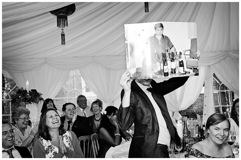 wedding guest holding up picture of groom with lots of wine bottles during speeches