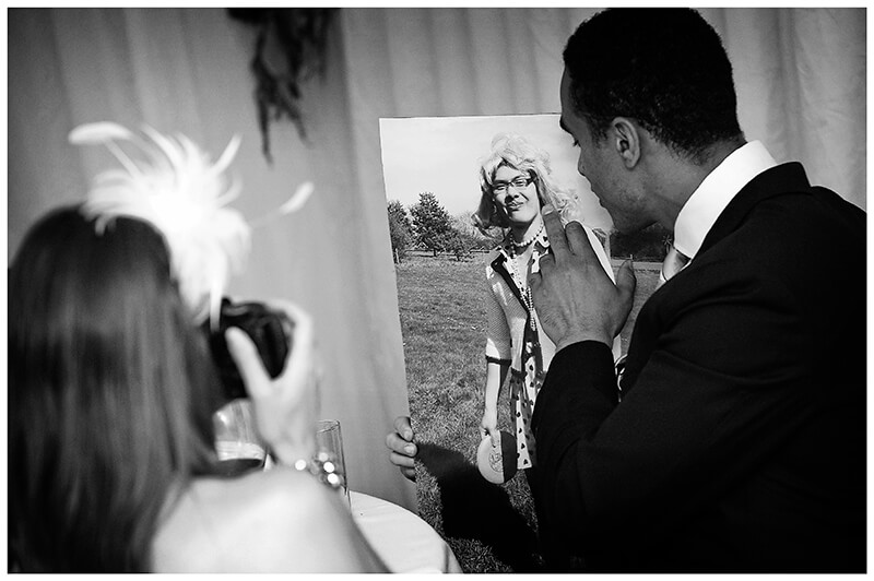 wedding guest looking at picture of groom dressed as a girl
