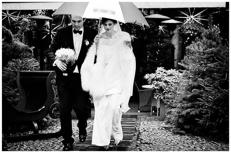 The George Stamford Bride and groom walking under umbrella