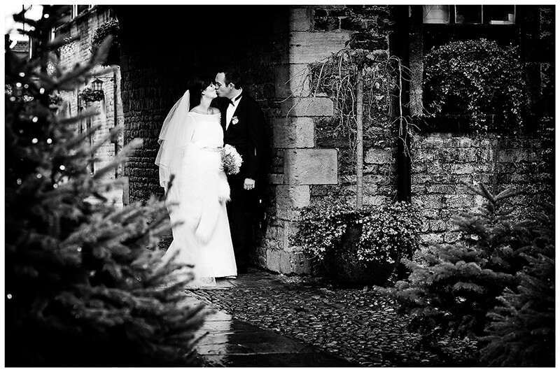 Bride and groom kiss standing under umbrella in the rain