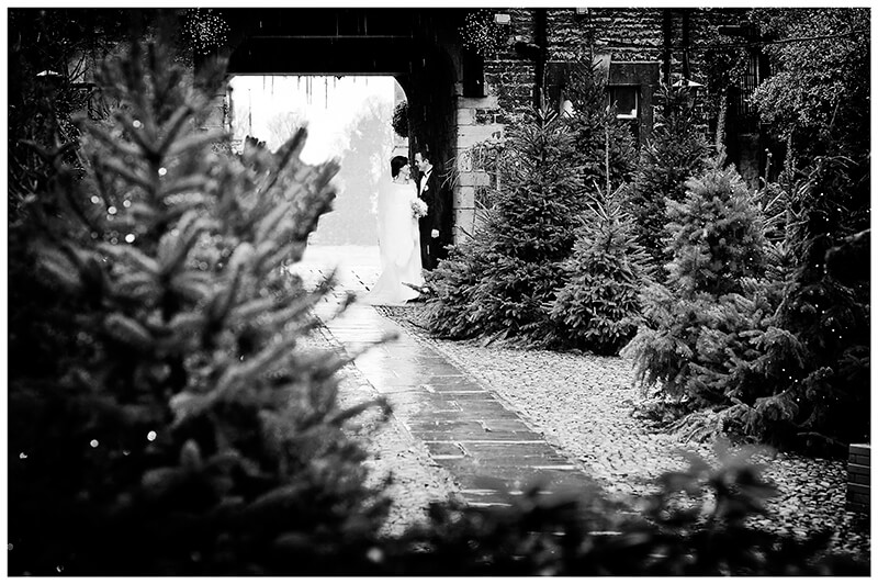 Bride and groom standing under arch at The George Stamford in the rain surrounded by christmas trees