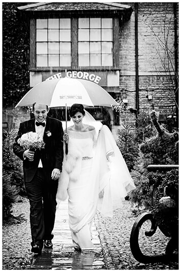 Bride and groom walking under umbrella in the rain at The George Stamford