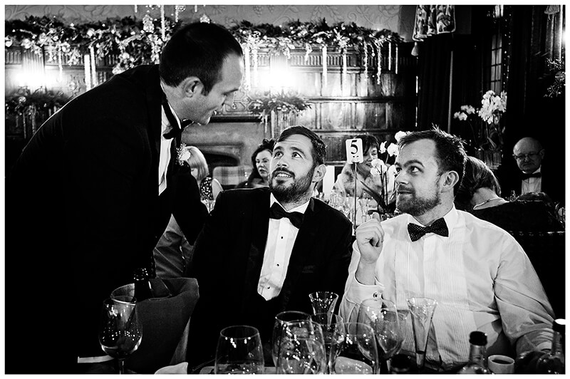 groom talking to two sitting male guests
