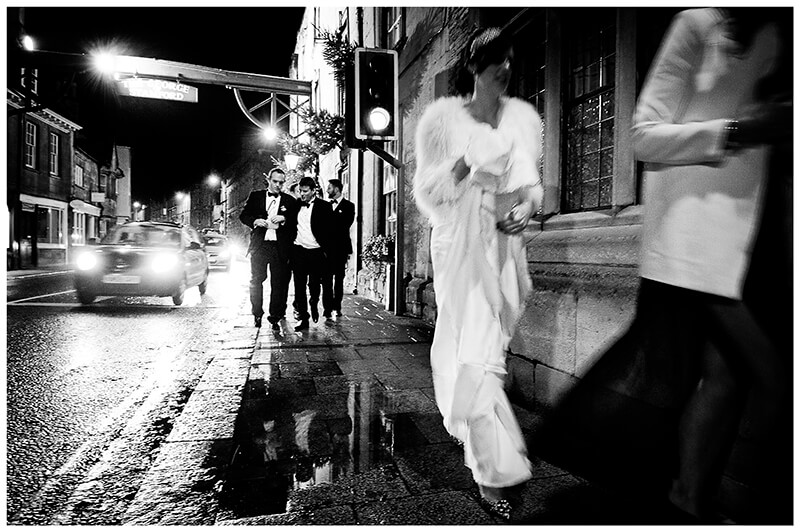 bride followed by grooms men walking down the street at night
