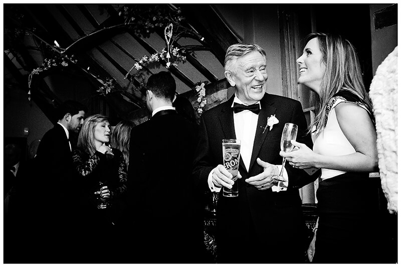 smiling older gent in tux talking to younger lady