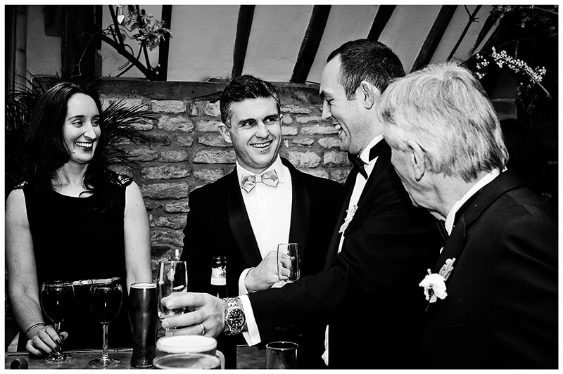 laughing groom with guests at the bar
