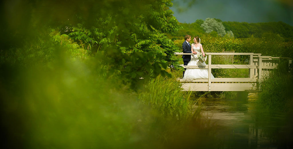Creative Oxfordshire Wedding Photographer happy couple standing on wooden Bridge in grounds of Friars Court