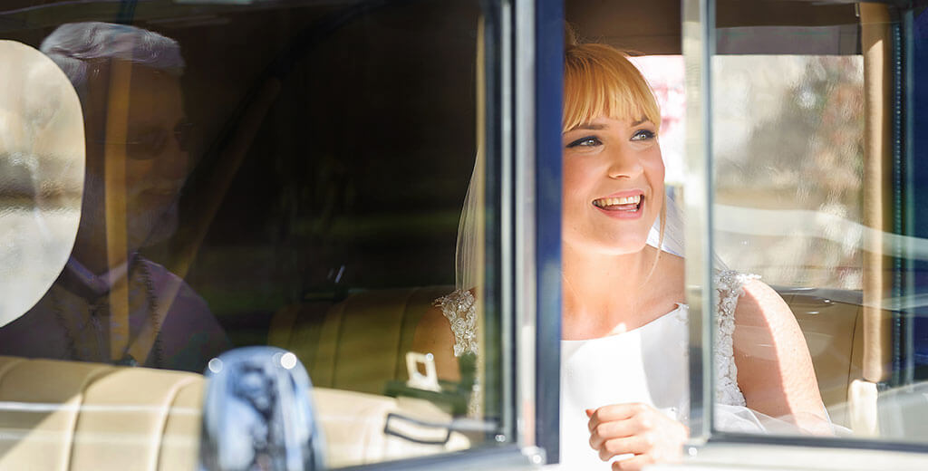 Creative Cambridge Wedding Photographer Bride arrives and smiles at vicar at Royal Windsor Chapel Surrey