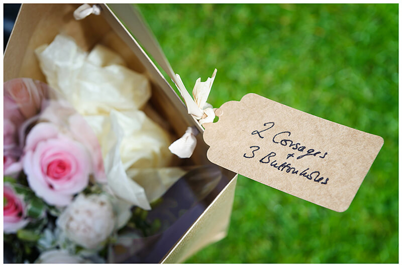 label on box for buttonholes and corsages attached to box for flowers