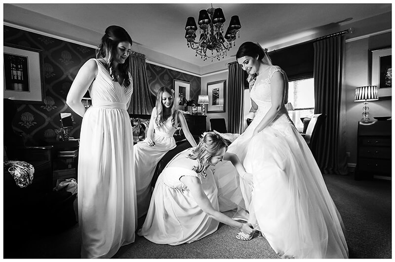Oxfordshire friars Court Wedding bridesmaid helps bride put on shoe as other bridemaids watch