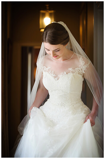 Oxfordshire friars Court Wedding bride holding dress walking down corridor