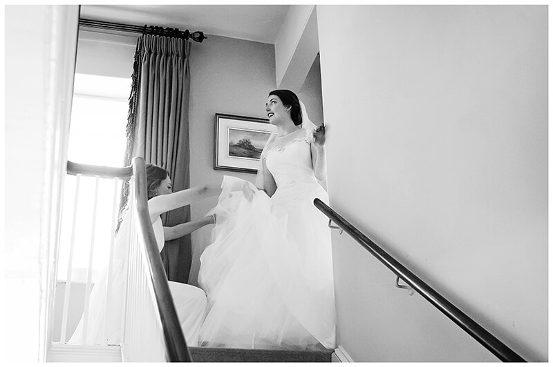 Oxfordshire friars Court Wedding bride at top of stairs looks out window as bridesmaid adjusts dress