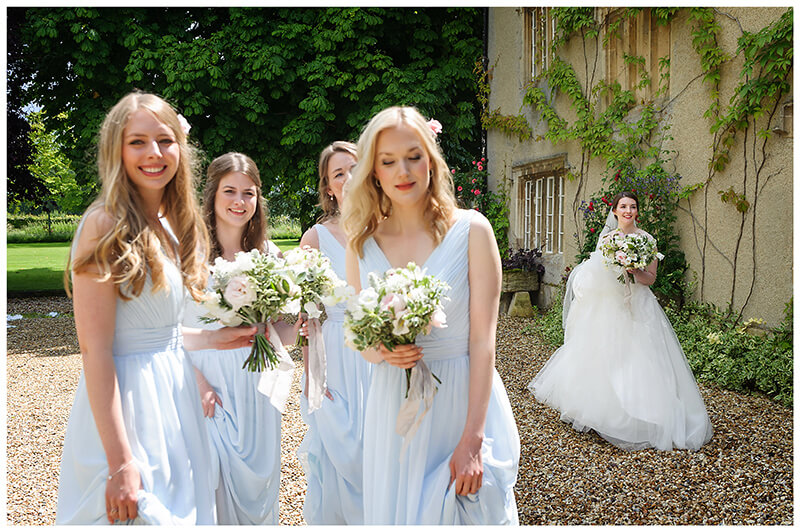 Oxfordshire friars Court Wedding bridesmaids in blue bride in background