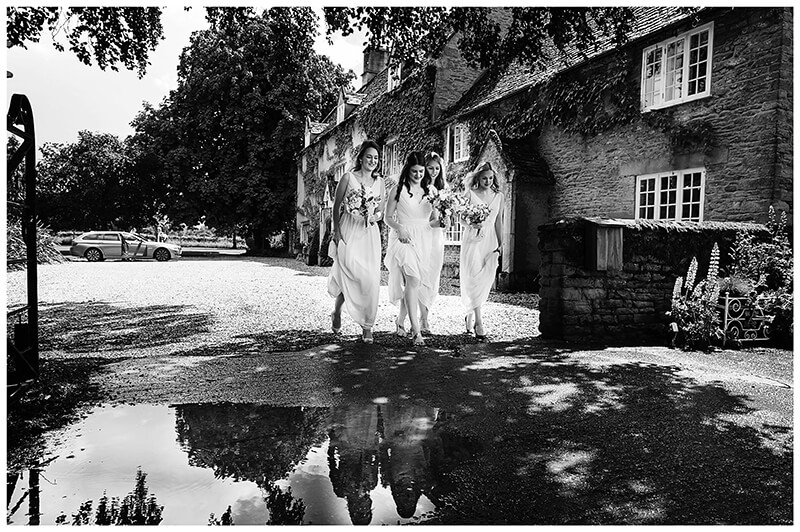 Oxfordshire friars Court Wedding bridesmaids walking around puddles to ceremony