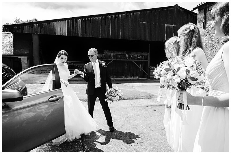Oxfordshire friars Court Wedding bride helped out of car by father as bridesmaids watch