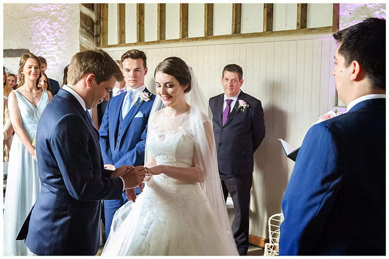 Oxfordshire friars Court Wedding groom places ring on brides finger