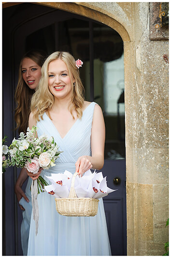 smiling bridesmaid holding basket of confetti at Oxfordshire friars Court Wedding
