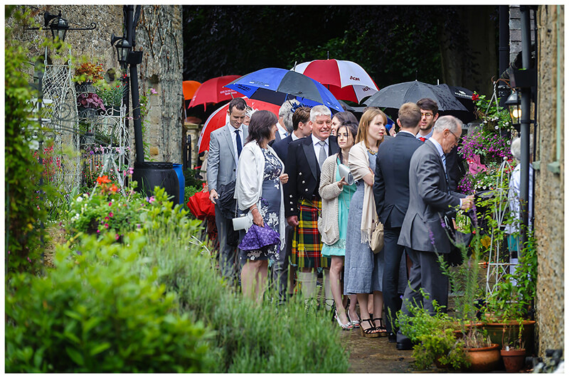 Wedding guests under umbrellas Que to enter house at Oxfordshire friars Court