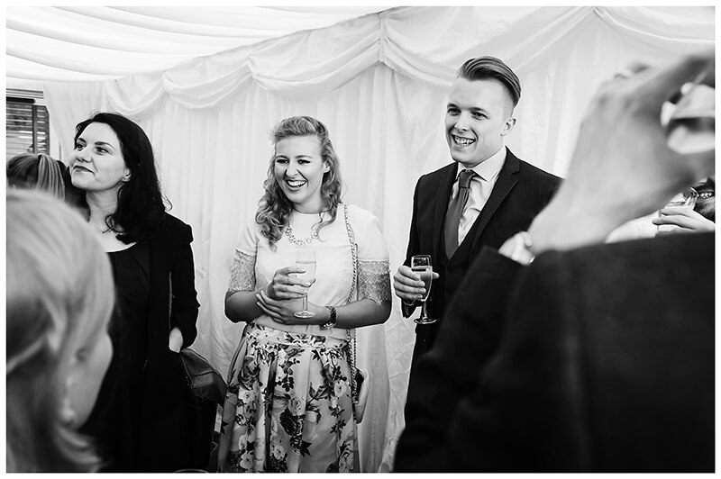 laughing and drink guests standing in marquee during friars Court wedding