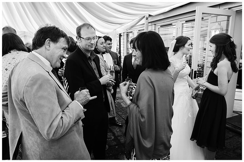Oxfordshire friars Court Wedding guests in conversation bride in background