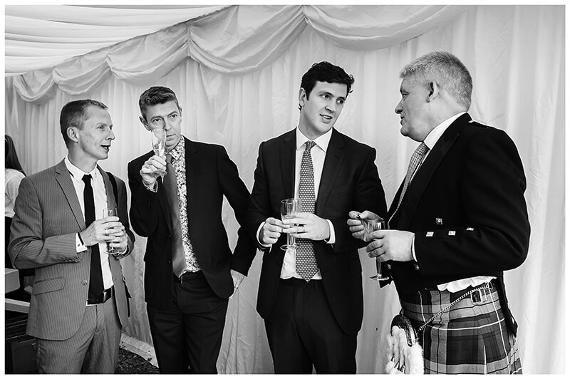 Oxfordshire friars Court Wedding four gents talking one in Scottish kilt