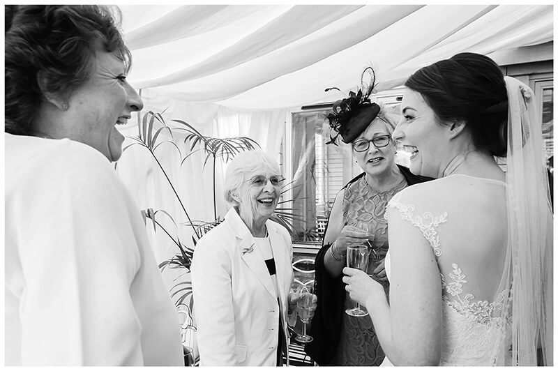 Oxfordshire friars Court Wedding Bride laughs as she talks to three ladies