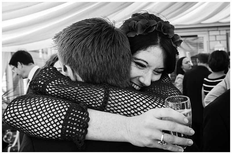 Oxfordshire friars Court Wedding female guest smiles as she give the groom a big hug
