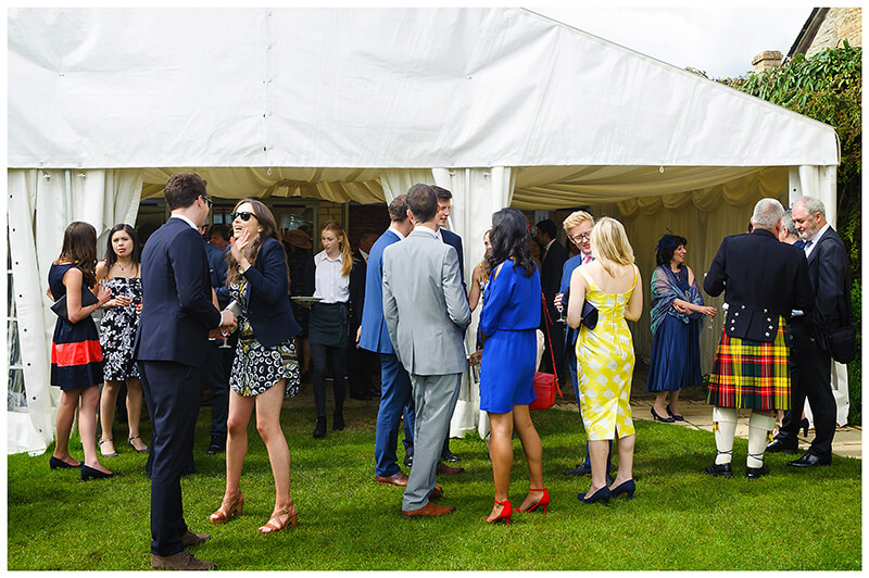 Oxfordshire friars Court Wedding guests in conversation outside marquee in garden