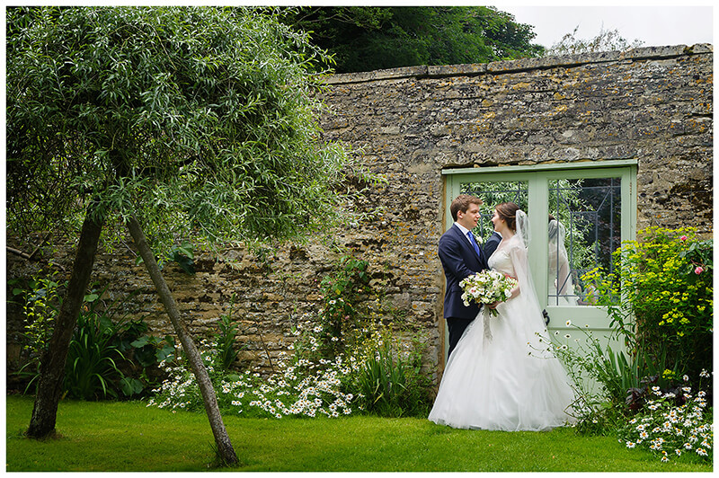 Oxfordshire friars Court Wedding bride groom embrace in front of door with mirrors in garden