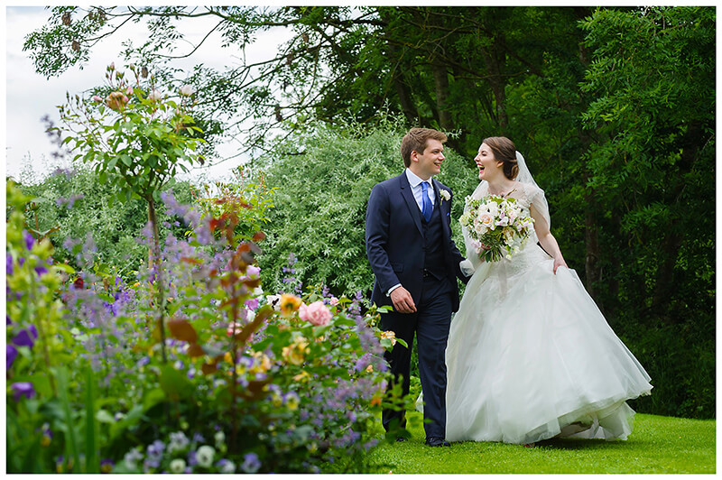 Oxfordshire friars Court Wedding bride groom laughing while they walking in gardens