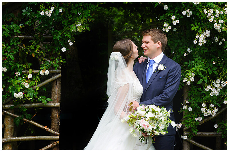Oxfordshire friars Court Wedding bride groom embrace in front of flower covered gazebo