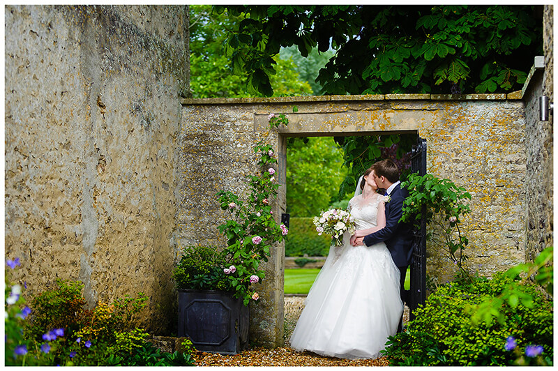 Oxfordshire friars Court Wedding bride groom kiss standing in arch way