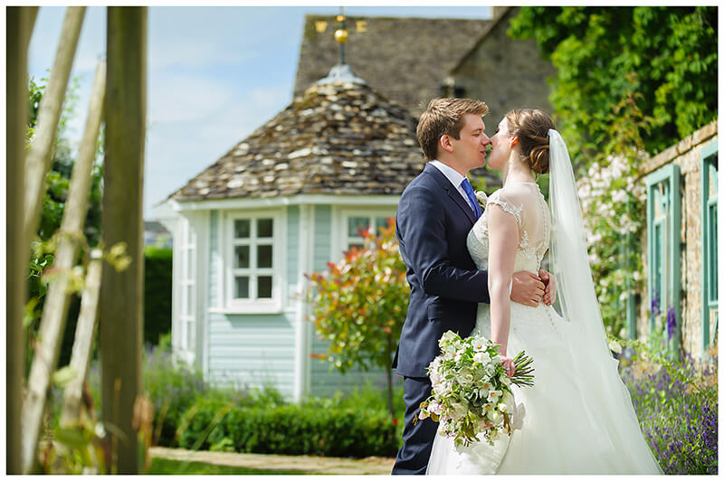 Oxfordshire friars Court Wedding bride groom kiss in front of blue wooden gazebo