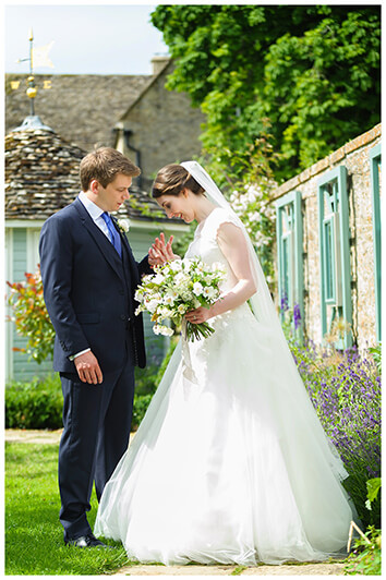 Oxfordshire friars Court Wedding bride groom look at each others wedding bands standing in gardens
