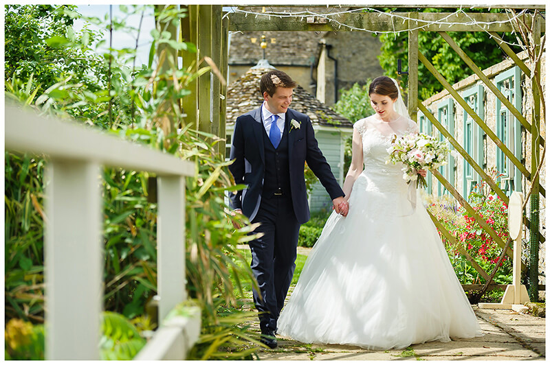 Oxfordshire friars Court Wedding bride groom hold hands walking through garden