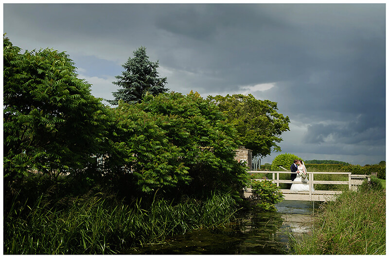 Oxfordshire friars Court Wedding bride groom standing on bridge under a dark sky