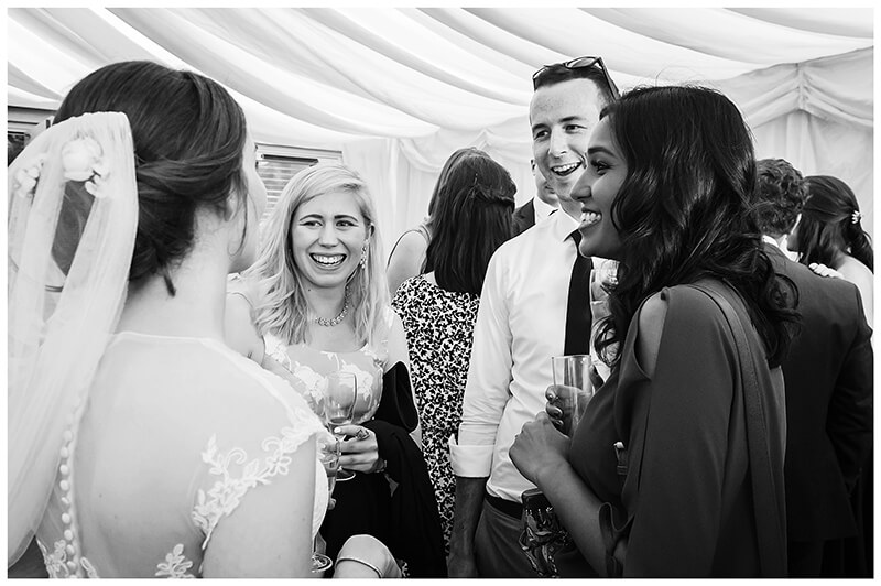 Oxfordshire friars Court Wedding smiling guests talking to bride