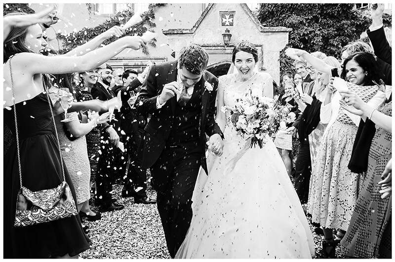 Oxfordshire friars Court Wedding groom ducks as confetti is thrown smiling bride