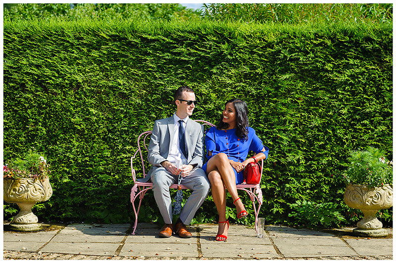 Oxfordshire friars Court Wedding couple sitting on bench against green hedge