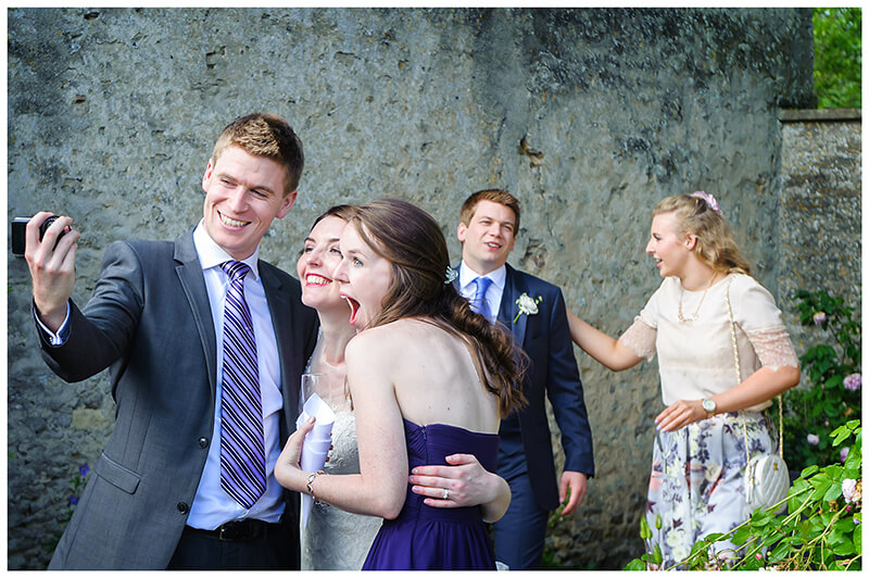 bride has selfie taken with a couple of guests
