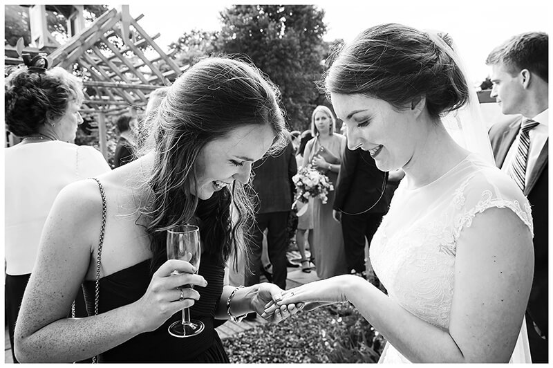 bride shows ring to female guest