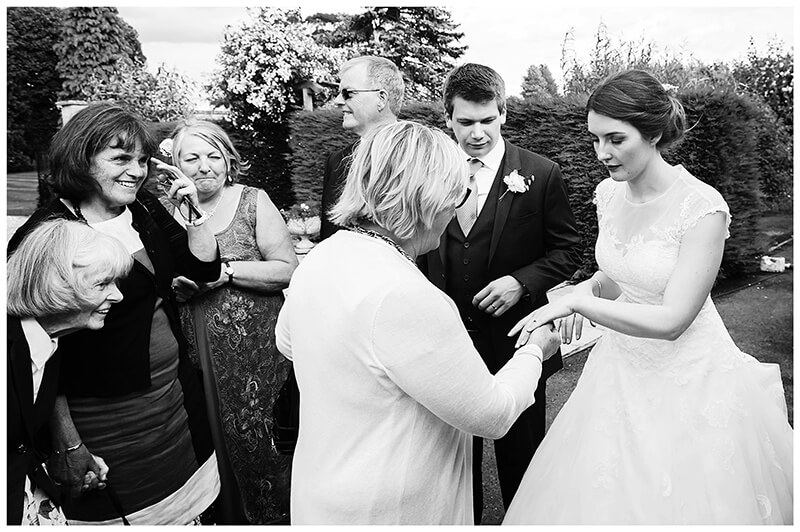 Oxfordshire friars Court Wedding bride shows ring ot female guest during receiving line
