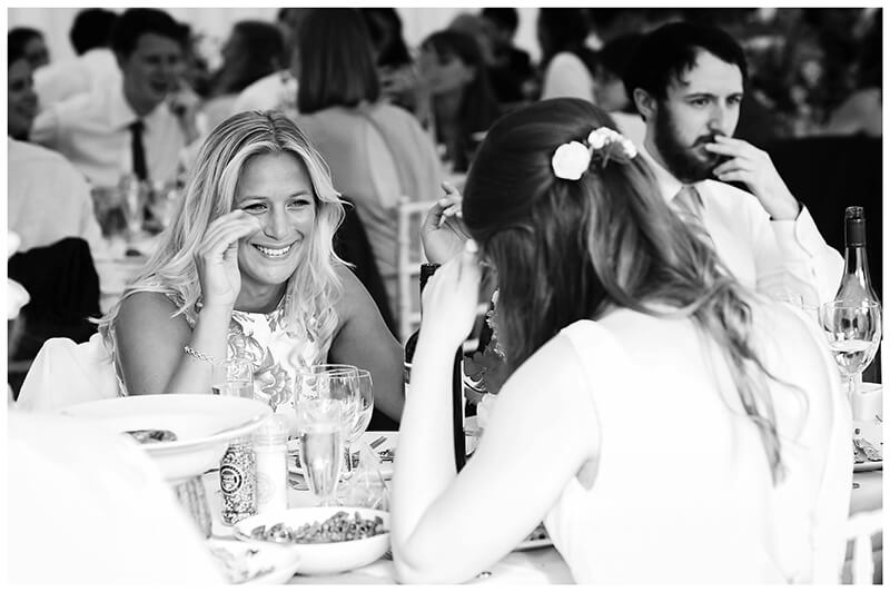laughing guests at dining table during reception at Oxfordshire friars Court Wedding
