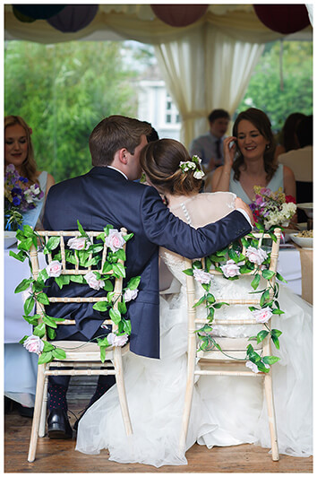 bride groom embrace whilst sat at dining table during reception at Oxfordshire friars Court Wedding