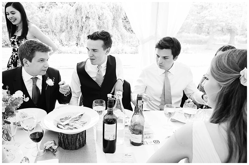 groom sitting at table talking to bestmen and bridesmaid during reception at Oxfordshire friars Court Wedding