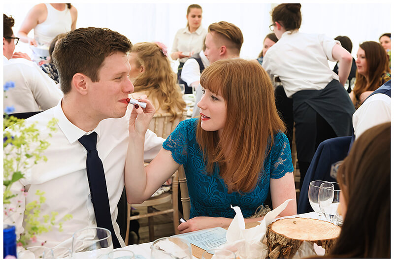 female wedding guest puts lipstick on male guest while sitting at dining table